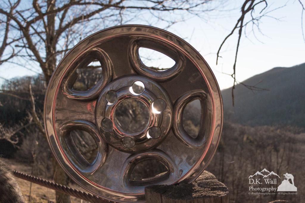 Sunset behind a hubcap.