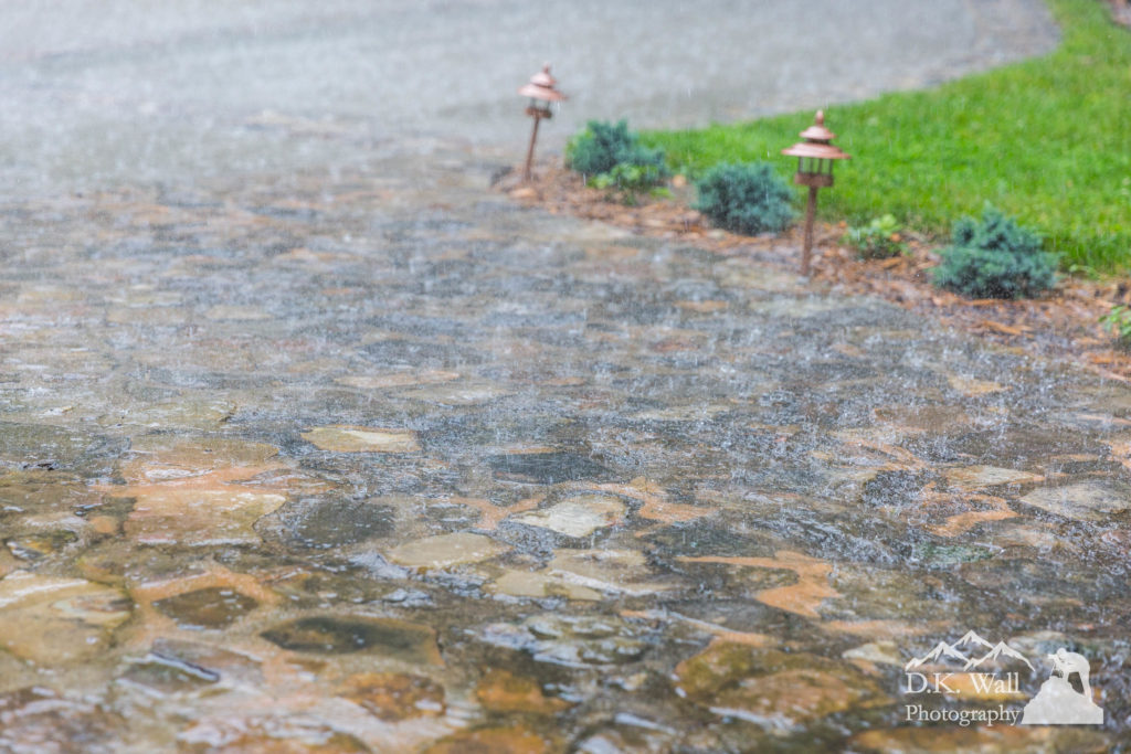 Rain bouncing off of a stone walkway in front of the house.