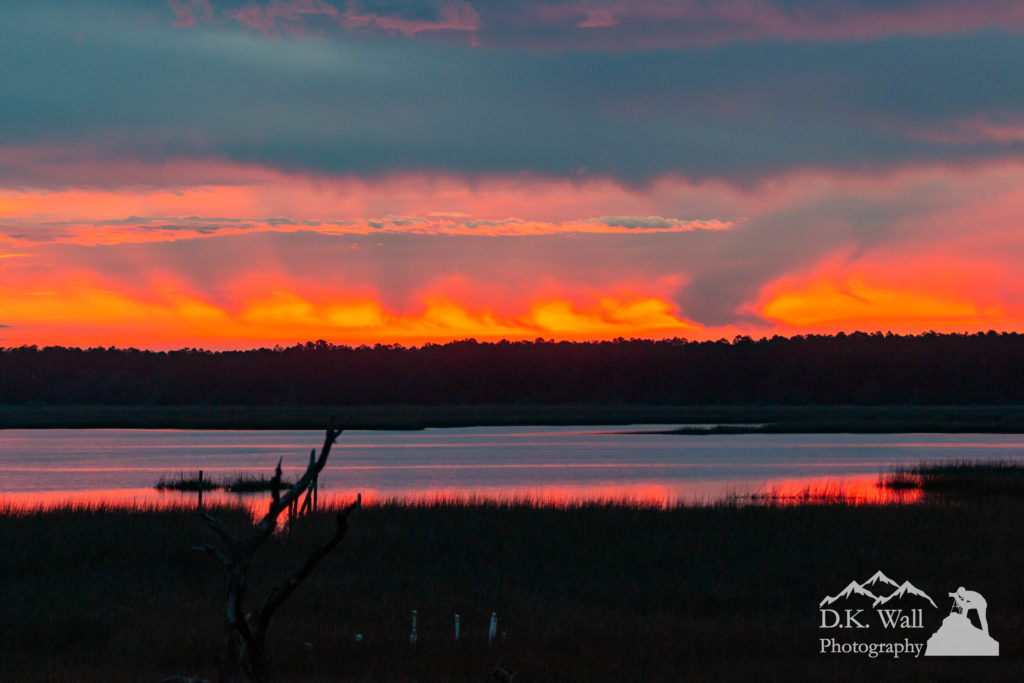Glowing sunrise over the salt marsh on a stormy morning.